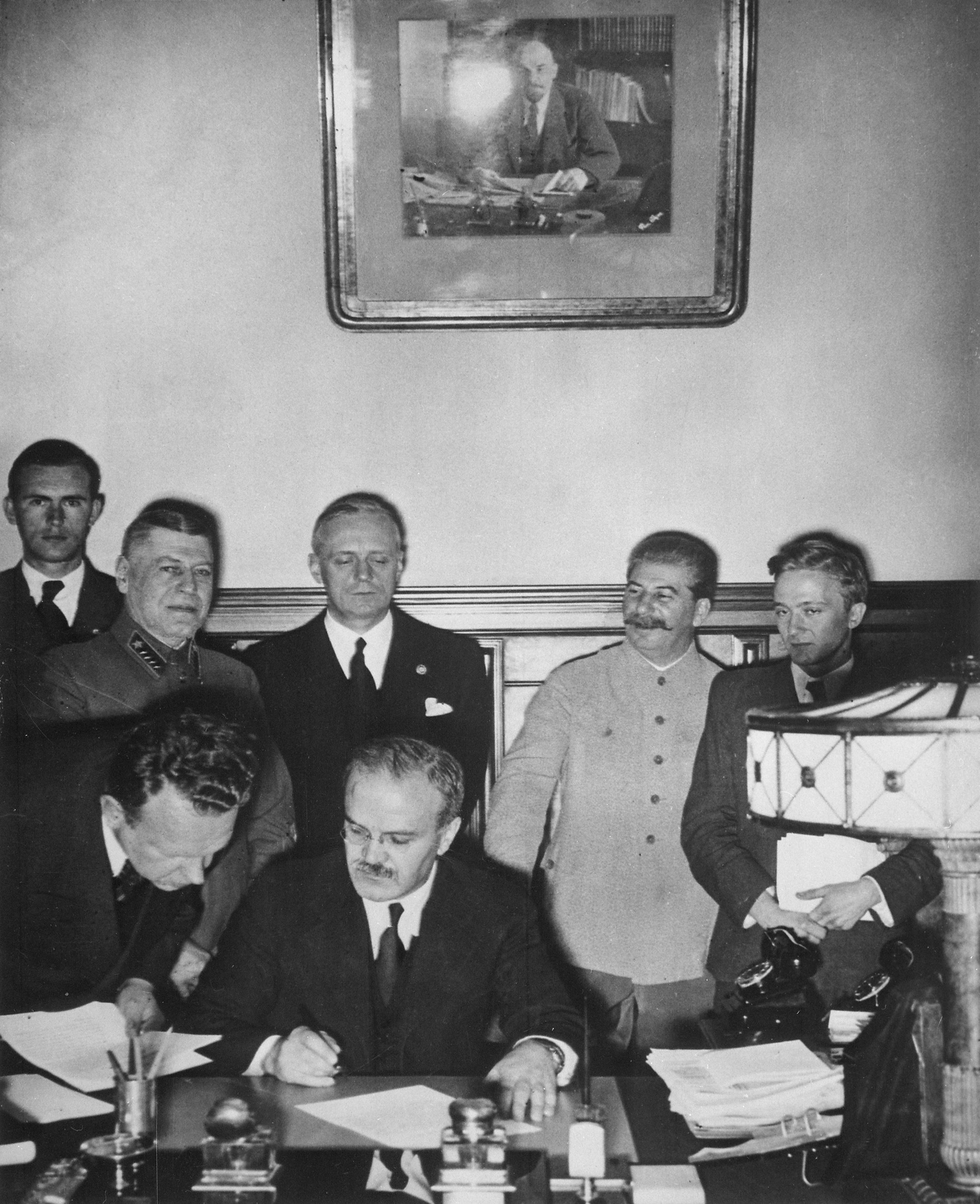 Подписание пакта Молотова-Риббентроппа. За спиной В.Молотова стоят Иоахим фон Риббентроп и Иосиф Сталин. Москва, 23 августа 1939 г.